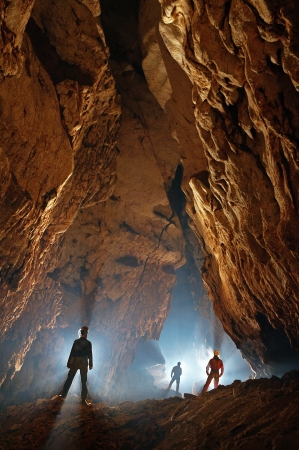 caving: Monumental cave hall with speleologists exploring it Stock Photo