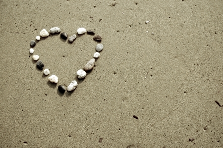 A Heart made of small stones on sand photo