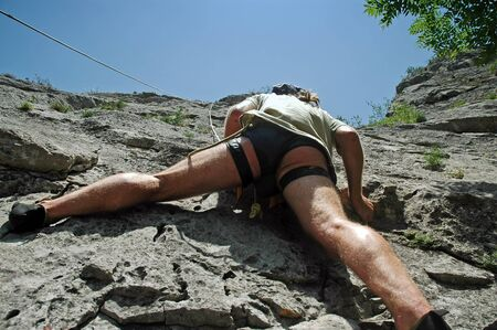Rock climber in action, climbing on a difficult cliff photo