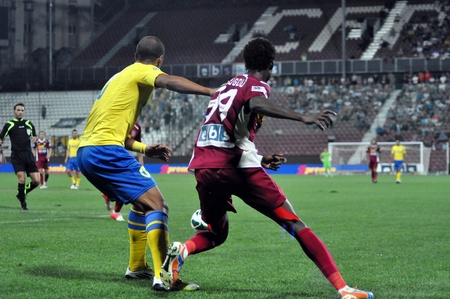 cfr cluj: CLUJ NAPOCA, ROMANIA - SEPTEMBER 2  Modou Sougou  in red  in action at a Romanian Championship soccer game, Petrolul Ploiesti  yellow  vs  CFR  red , final score 2-2, on Sept 2, 2012 in Cluj, Romania