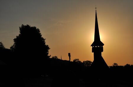 Silhouette of a church tower in the sunset photo
