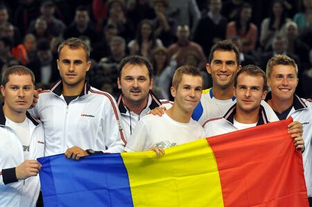 florin: The Davis Cup match final, Romania wins against Denmark in EuropeAfrica1st Round. The Romanian players are celebrating the victory with the Romanian flag