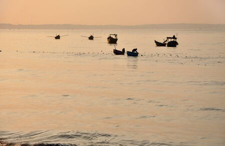 Fishing vessels on the sea at sunrise, Mui Ne, Vietnam photo