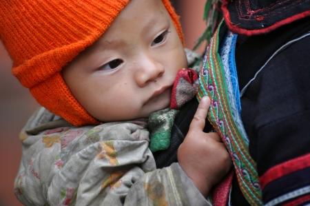 A Black Hmong Vietnamese woman carrying her child, Sapa, Vietnam
