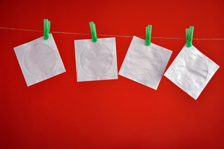 Paper CD envelopes hanging clipped on the rope in front of a red background  photo