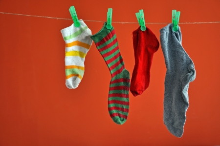 Different types of striped socks hanging on a rope isolated on red  photo