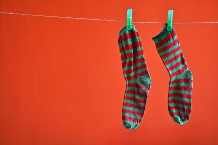 Paar gestreepte sokken opknoping op een touw geïsoleerd op rood Stockfoto