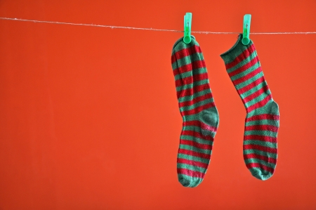 Pair of striped socks hanging on a rope isolated on red