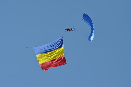 parachutists: Parachutists flying in the air with a Romanian flag at the Romanian Air Fest on May 18, 2013 in Cluj Napoca, Romania