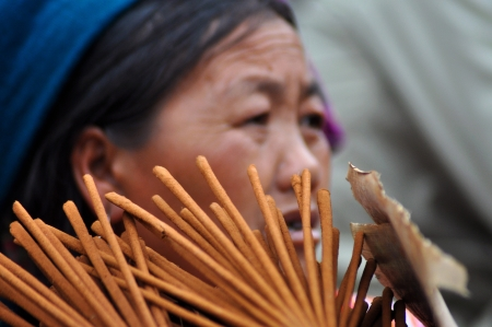 A Hmong seller woman in traditional clothes selling incense sticks in Bac Ha, Sa Pa, Vietnam