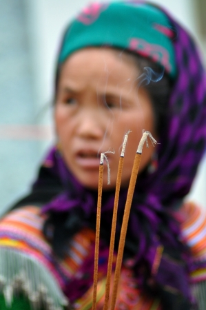 A Hmong seller woman in traditional clothes selling incense in Bac Ha, Sa Pa, Vietnam