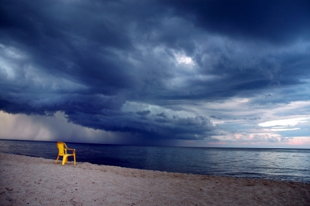 paisaje mediterraneo: Silla amarilla en la playa, el clima tormentoso que viene Foto de archivo