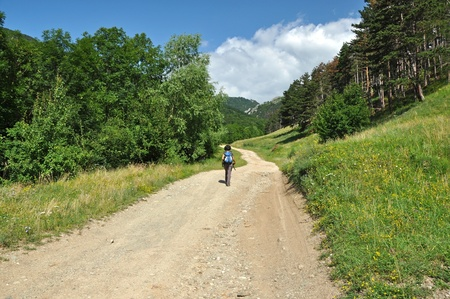Winding dirt lane, mountain road with a trekking woman photo