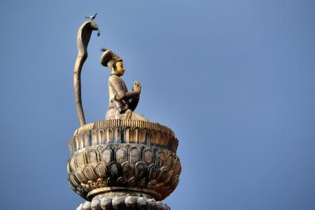 King Yoganarendra Malla bronze statue, under cobra snake, flanked by his wives, over stone column  Durbar square  Patan, Kathmandu, Nepal  Imagens