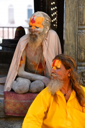 KATHMANDU, NEPAL - OCTOBER 8  Holy Sadhu men with dreadlocks and traditional painted face resting at Pashupatinath Temple  On October 8, 2013 in Kathmandu, Nepal