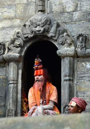 KATHMANDU - OCT 8  Nepalese Sadhu man with traditional painted face resting at Pashupatinath Temple  Tourism has drawn many alleged fake sadhus to Pashupatinath   On Oct 8, 2013 in Kathmandu, Nepal Stock Photo - 23384385