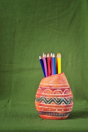 Color pencils in a pot, isolated on green  photo