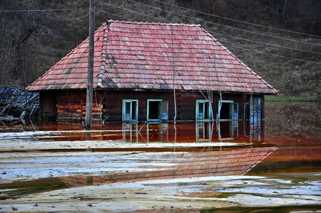 Ecological disaster  An abandoned village flooded by polluted water from a copper open pit mine Stock Photo - 24037114