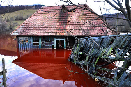 Ecological disaster  An abandoned village flooded by polluted water from a copper open pit mine Stock Photo - 24037120