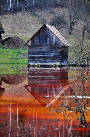 open cast mine: An abandoned house flooded by polluted water from a copper open cast mine  Stock Photo