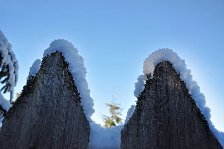 Wooden fence in winter with snow and ice crystals on top photo