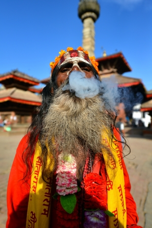 KATHMANDU - OCT 10  Sadhu man smoking a cigarette in the Durbar square  On Oct 10, 2013 in Kathmandu, Nepal  Sadhus are holy men who are focusing on the spiritual practice of Hinduism  Stock Photo - 24484166