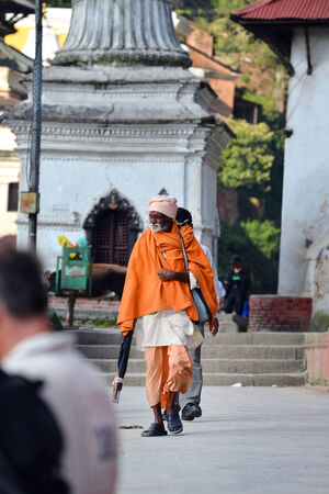 KATHMANDU - OCT 8  Nepalese Sadhu man seeking alms at Pashupatinath Temple  Tourism has drawn many alleged fake sadhus to Pashupatinath  On Oct 8, 2013 in Kathmandu, Nepal