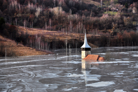 Abandoned church in a mud lake  Natural mining disaster with water pollution  Geamana, Romania photo
