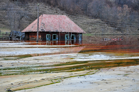 Ecological disaster  An abandoned village flooded by polluted water from a copper open pit mine Stock Photo - 24914810