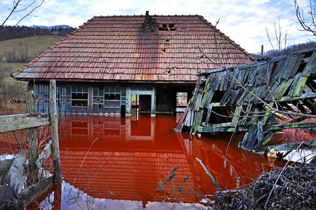 Ecological disaster  An abandoned village flooded by polluted water from a copper open pit mine Stock Photo - 24914788