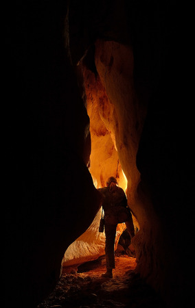 Underground cave passage with a caver discover it Stock Photo - 26238263
