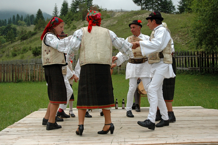 ethnography: GHIMES, ROMANIA - JUNE 3  A group of dancers in traditional costumes dancing at a wedding in Ghimes, Transylvania  Traditions in Transylvania area are well kept  June 3, 2005 in Ghimes, Romania  Editorial