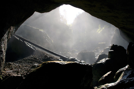 abseiling: A foggy, dark cave entrance silhouette in Padis, Romania  Stock Photo
