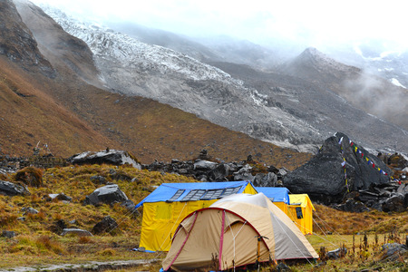 Expedition tents in the Annapurna Base Camp, Himalaya mountains, Nepal in a cloudy day photo