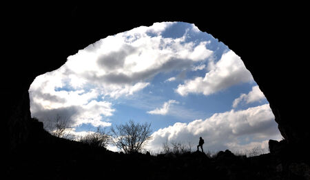 A rock arch and silhouette of a cave entrance photo