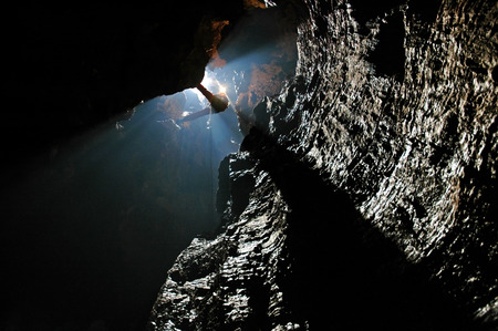 Spelunker abseiling in a cave on a rope photo