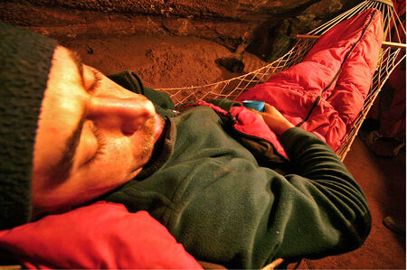 sleeping bag: A spelunker resting in a hammock  in a sleeping bag, in a cave
