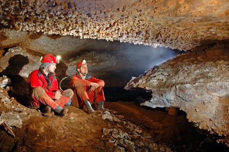Spelunkers in de grot bewonderen van de stalactieten