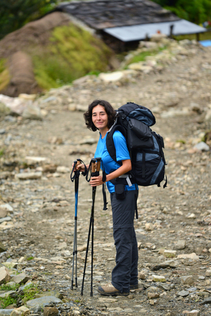 A young woman with a backpack trekking in the Himalayas, Nepal