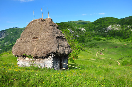 Wooden stable with thatched roof in the mountains photo