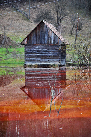 Abandoned house floodedby polluted water from a copper mine  photo