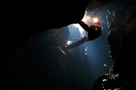 Spelunker abseilen aan een touw in een sinkhole