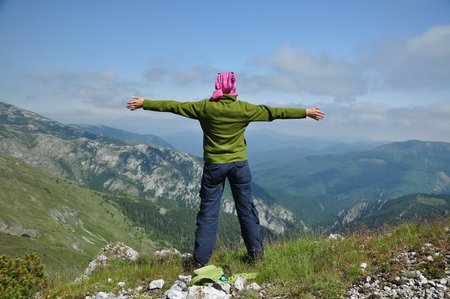 woman hiking: Young woman standing on a cliff and looking to the sky with raised hands