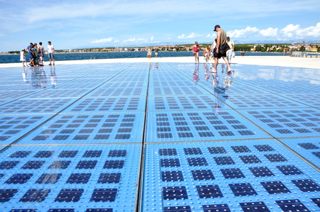 ZADAR - AUGUST 25: People walking on Greeting to the Sun sculpture. It  consists of 300 multilayer glass panels and uses solar power to create a light show that displays at night. On August 25, 2014 in Zadar, Croatia