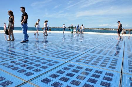 multilayer: Zadar - 25 de agosto: Personas caminando en Saludo al Sol escultura. Se compone de 300 paneles de vidrio de m�ltiples capas y utiliza la energ�a solar para crear un espect�culo de luces que se muestra en la noche. El 25 de agosto de 2014 en Zadar, Croacia