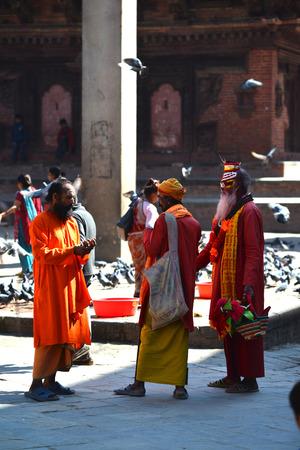 KATHMANDU - OCT 10: Shaiva sadhu men seeking alms in the Durbar square. On Oct 10, 2013 in Kathmandu, Nepal. Sadhus are holy men who are focusing on the spiritual practice of Hinduism
