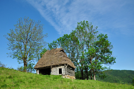 Wooden stable with thatched roof in the mountains. Transylvania, Romania photo