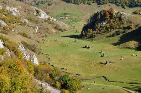 Autumn mountain landscape with haystacks in a valley. Romania photo