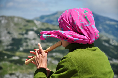 Girl with pink scarf playing on flute in the mountains