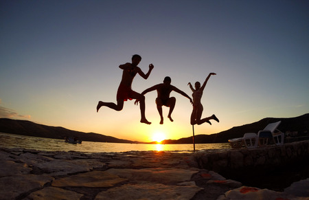 Silhouette of friends jumping at sunset on the beach photo